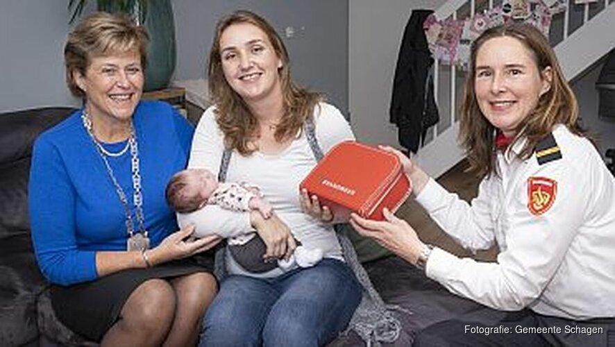 Burgemeester geeft namens brandweer geboortekoffer aan ouders